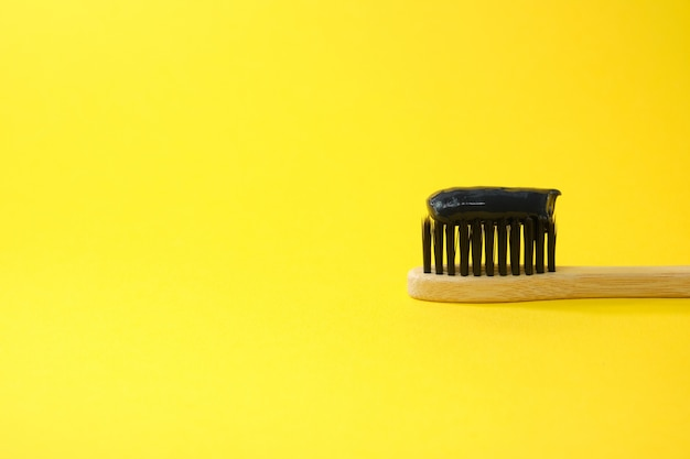 黄色の背景に黒い木炭の歯磨き粉と歯ブラシ