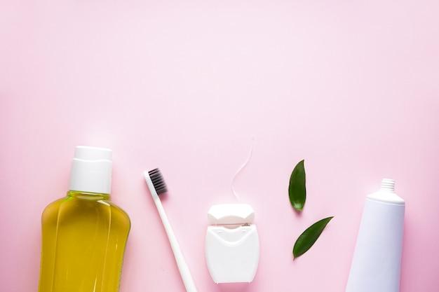 Зубная щетка с ополаскивателем для рта на розовом