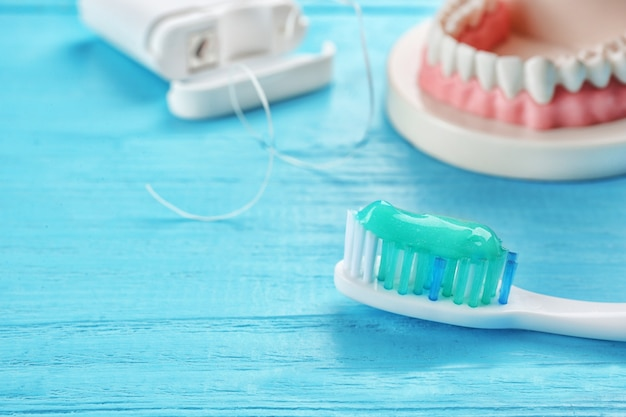 Toothbrush with paste on color wooden surface, closeup