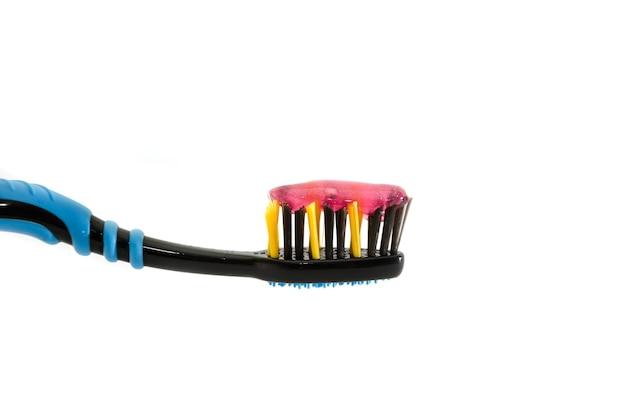 白で隔離されるペーストが付いている歯ブラシ。