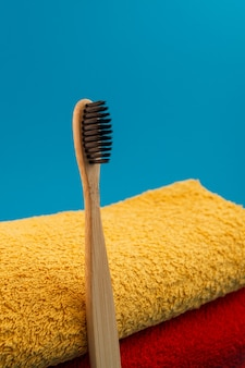 Toothbrush with red and yellow towel on blue background