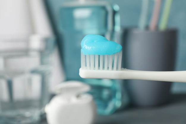 Toothbrush with toothpaste on surface with dental care tools