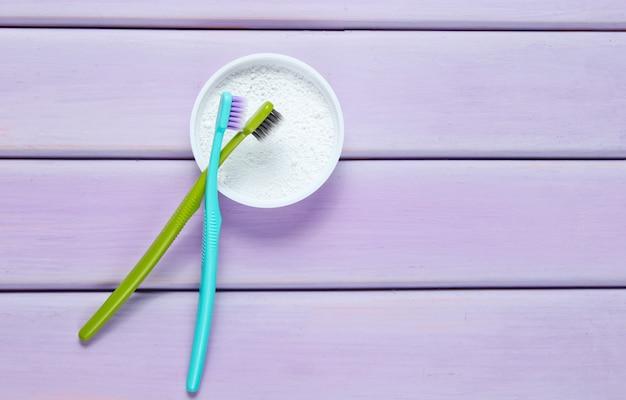Зубные щетки и зубной порошок, изолированные на фиолетовом