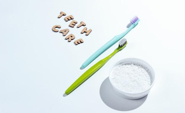 白で隔離される歯ブラシと歯のパウダー