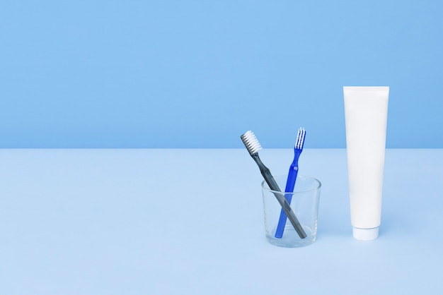 青の背景に歯ブラシと歯磨き粉のチューブ。歯の衛生の概念。フラットレイ。モックアップコンセプトをブランディングするためのナチュラルビューティー製品。テキストを追加します。