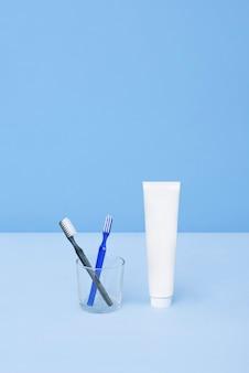 Зубные щетки и тюбик зубной пасты на синем фоне концепция гигиены зубов натуральные косметические продукты для брендинга концепции макета добавьте свой текст