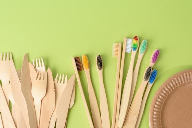 Зубные щетки, деревянная вилка и пустая круглая одноразовая тарелка коричневого цвета из переработанных материалов на зеленой поверхности, вид сверху