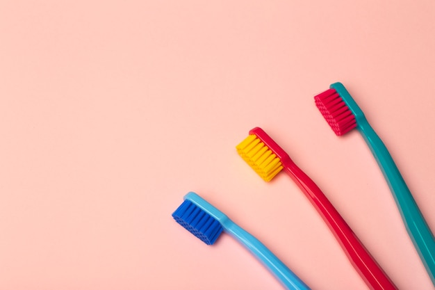 Toothbrushes of different colors on pink b