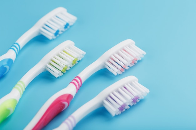 Toothbrushes of different colors in a row on a blue surface