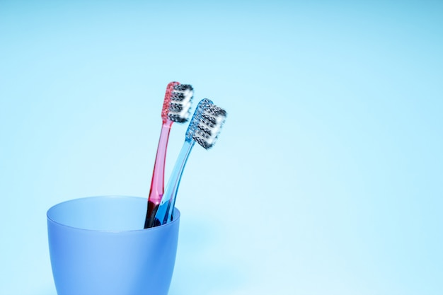 Toothbrushes in a glass, blue background. copy space