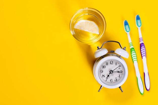歯ブラシ、レモンと目覚まし時計と水のガラス