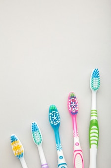 Toothbrushes on grey background with copy space.