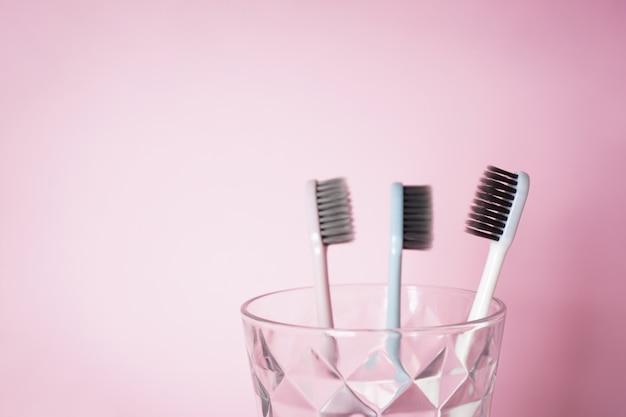 Зубные щетки в стакане на розовом