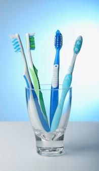 Зубные щетки в стекле на цветном фоне