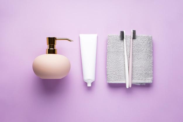 Зубные щетки на полотенце и дозатор крема на розовом