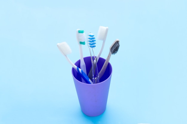 Toothbrushes in plastic glass on blue space. copy space