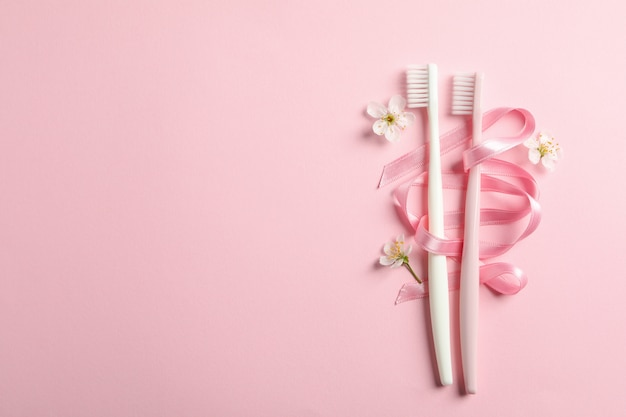 Toothbrushes, ribbon and flowers on pink surface