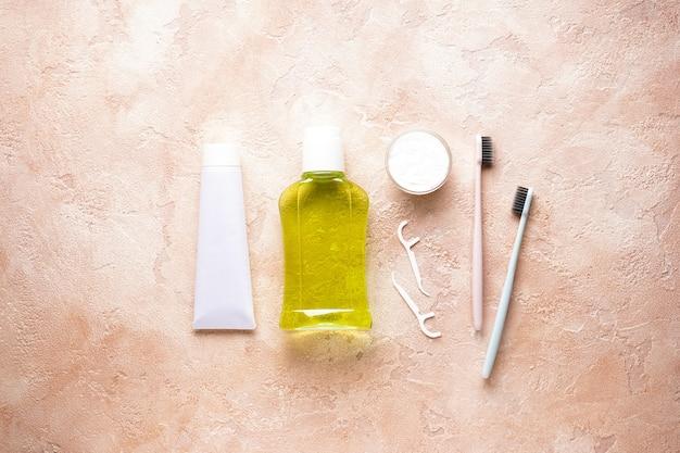 Зубные щетки, зубная паста и жидкость для полоскания рта на бежевом
