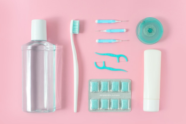 Toothbrushes, toothpaste, rinse and chewing gum set on pink background