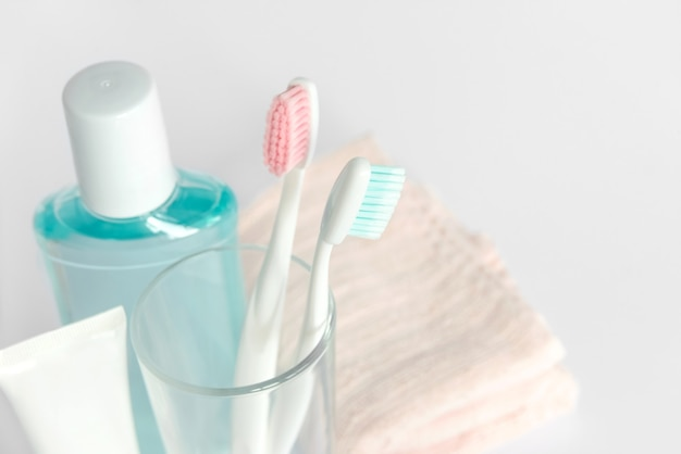 Toothbrushes, toothpaste, rinse and towel on white background