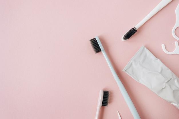 분홍색에 칫솔, 치약, 치실. 평면 위치, 상위 뷰 구강 관리, 치과 위생 개념