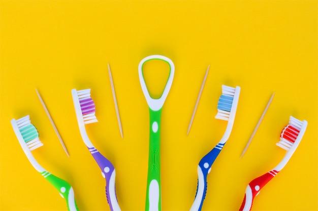 Зубные щетки, зубочистка, скребок для языка на желтом фоне. вид сверху.