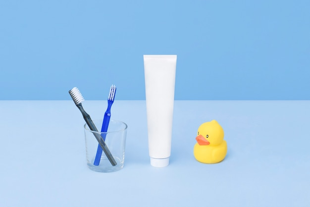 Toothbrushes and tube of toothpaste with rubber yellow duck on blue background. teeth hygiene concept. flat lay. natural beauty products for branding mockup concept. add your text.