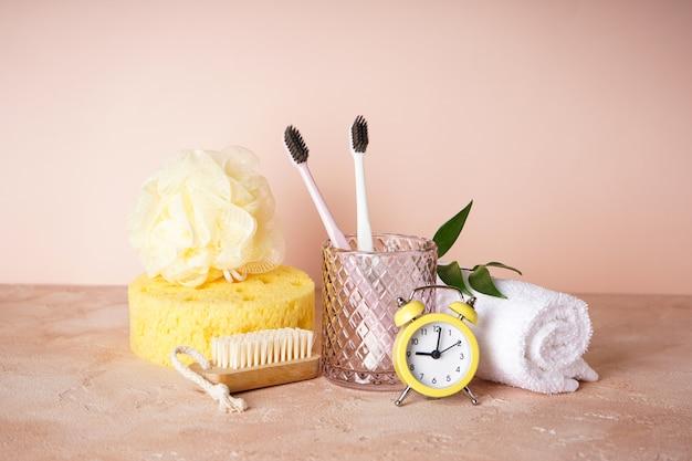 Зубные щетки с черной щетиной в стакане с банными принадлежностями и будильник на бежевом
