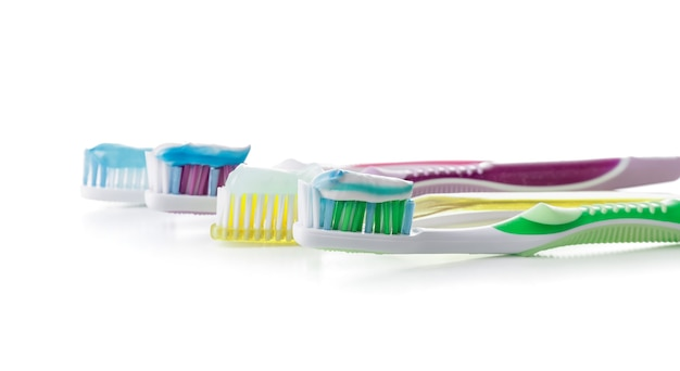 Зубные щетки с пастой на белом фоне
