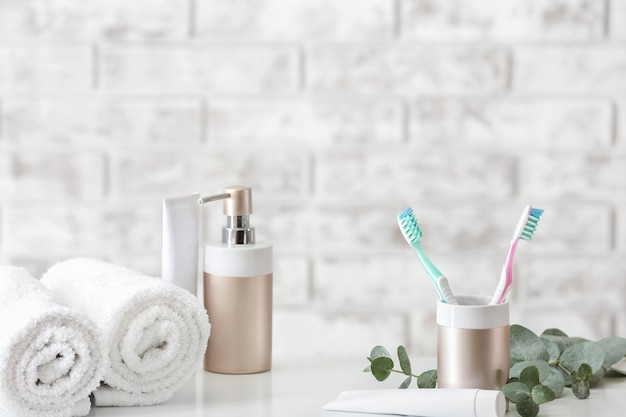 Toothbrushes with paste, towels and soap on table in bathroom