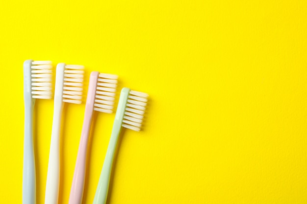 Toothbrushes on yellow background, space for text