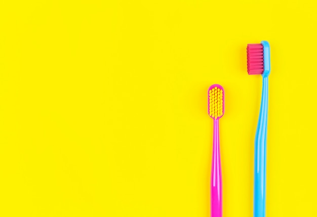Toothbrushes on a yellow background with place for text