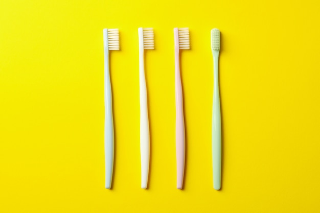 Toothbrushes on yellow surface. dental care