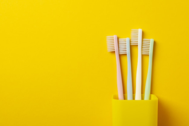 Toothbrushes on yellow surface