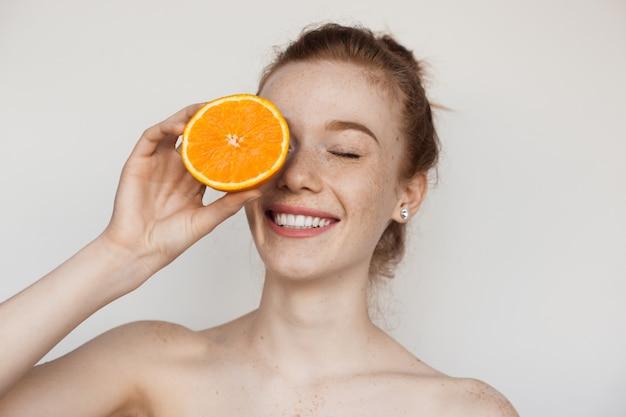 Зубастая улыбающаяся кавказская дама с веснушками и рыжими волосами прикрывает глаз нарезанным апельсином и позирует с обнаженными плечами