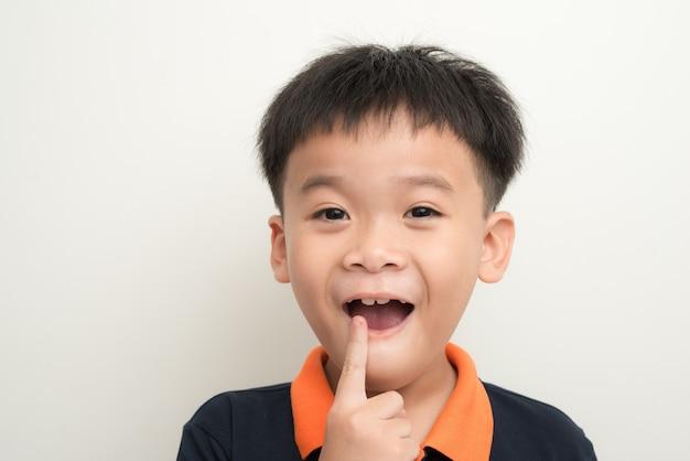 Беззубый улыбающийся мальчик, показывающий свое потерянное зубное молоко
