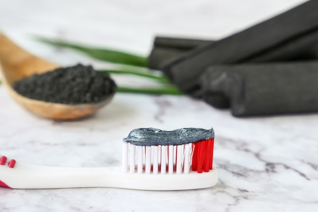 Toothpaste by activated charcoal powder on marble table