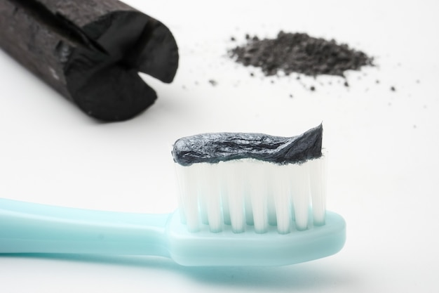 Toothpaste by activated charcoal powder on white background