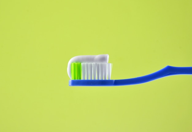 青色の明るい背景に青い歯ブラシのクローズアップの歯磨き粉