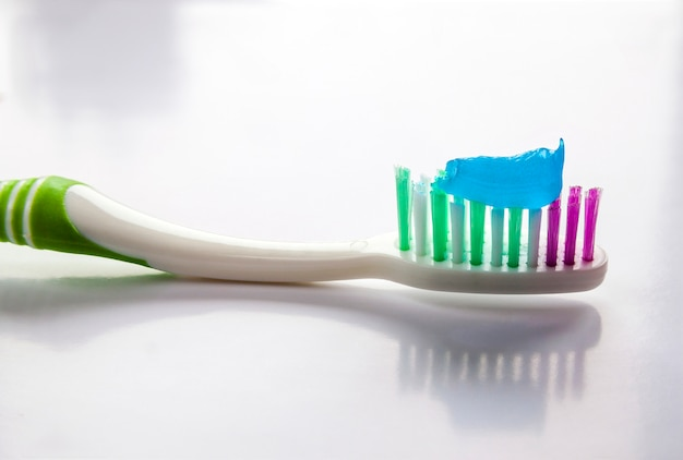 Toothpaste on a toothbrush close-up on a white light background