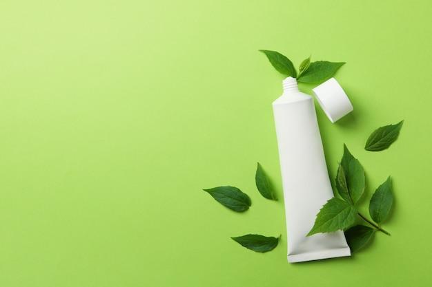 Тюбик зубной пасты и листья мяты на зеленой поверхности