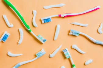 Toothpaste with different type of toothbrushes on colored background