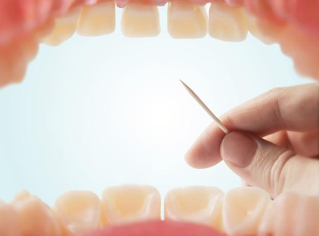 Зубочистка в руке - вид изо рта