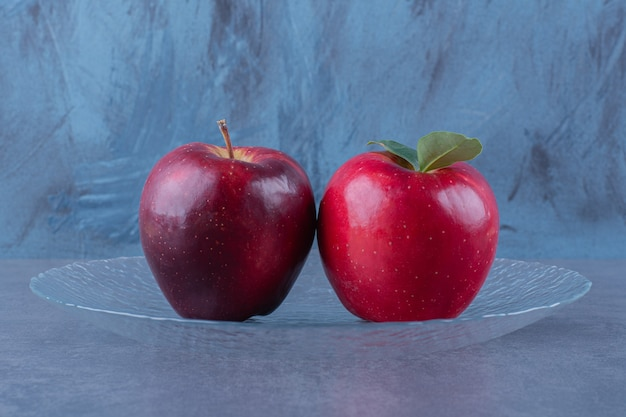 Toothsome apples on a glass plate on the dark surface