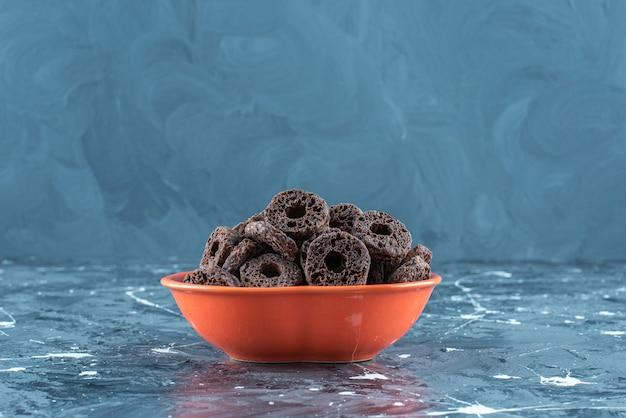 大理石の背景に、ボウルにチョコレートでコーティングされた歯ごたえのあるコーンリング。