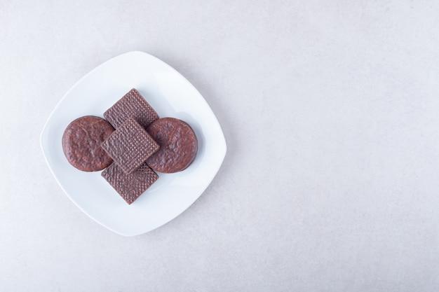 대리석 테이블에 접시에 이쑤시개 초콜릿 덮인 쿠키와 웨이퍼.