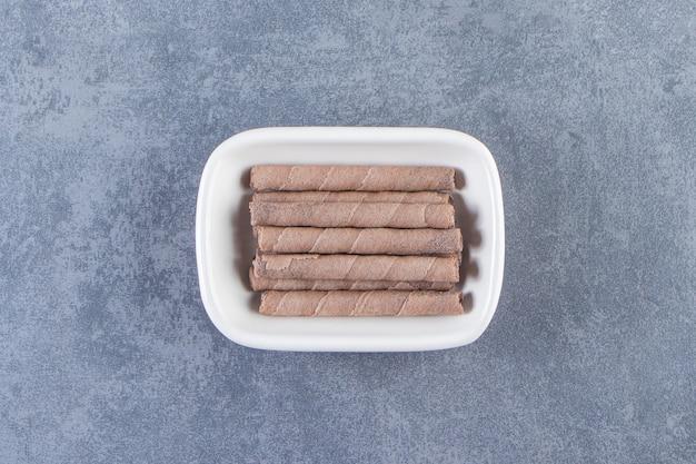 Зубастый шоколадный вафельный рулет в миске на мраморном фоне.