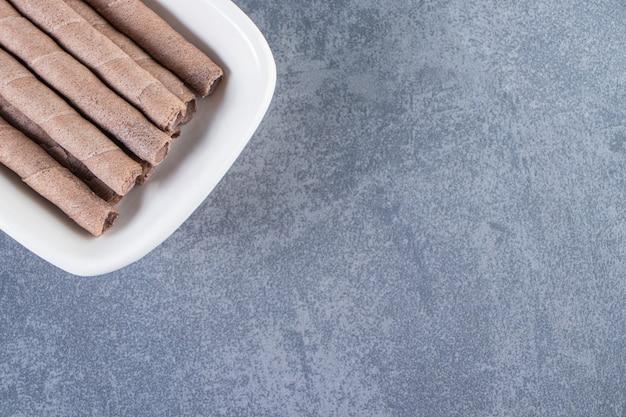 대리석 표면에 있는 그릇에 있는 이쑤시개 초콜릿 웨이퍼 롤