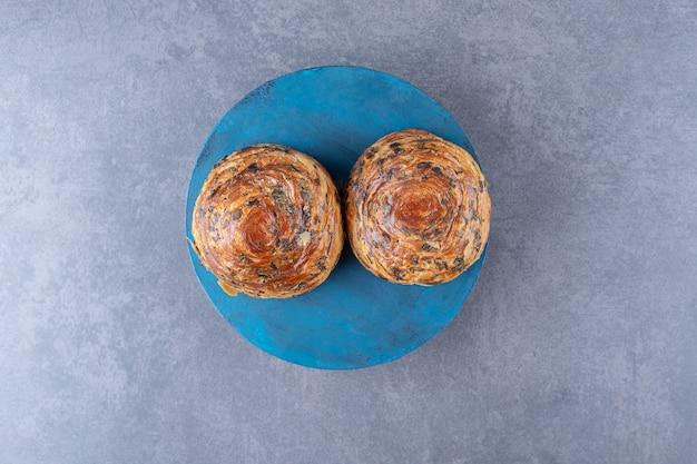 大理石のテーブルの上の皿の上の歯ごたえのあるクッキー。