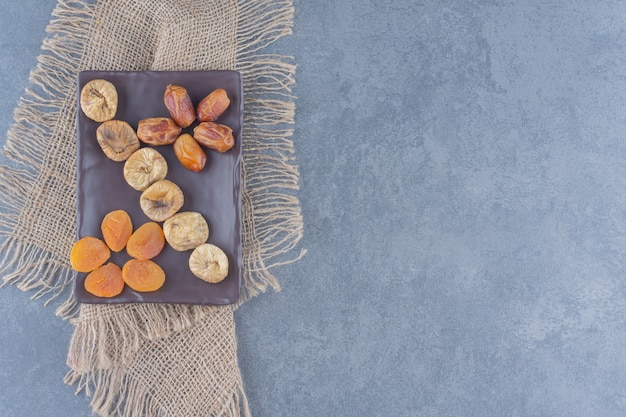 Toothsome dried fruits on the board, on the trivet, on the marble background.